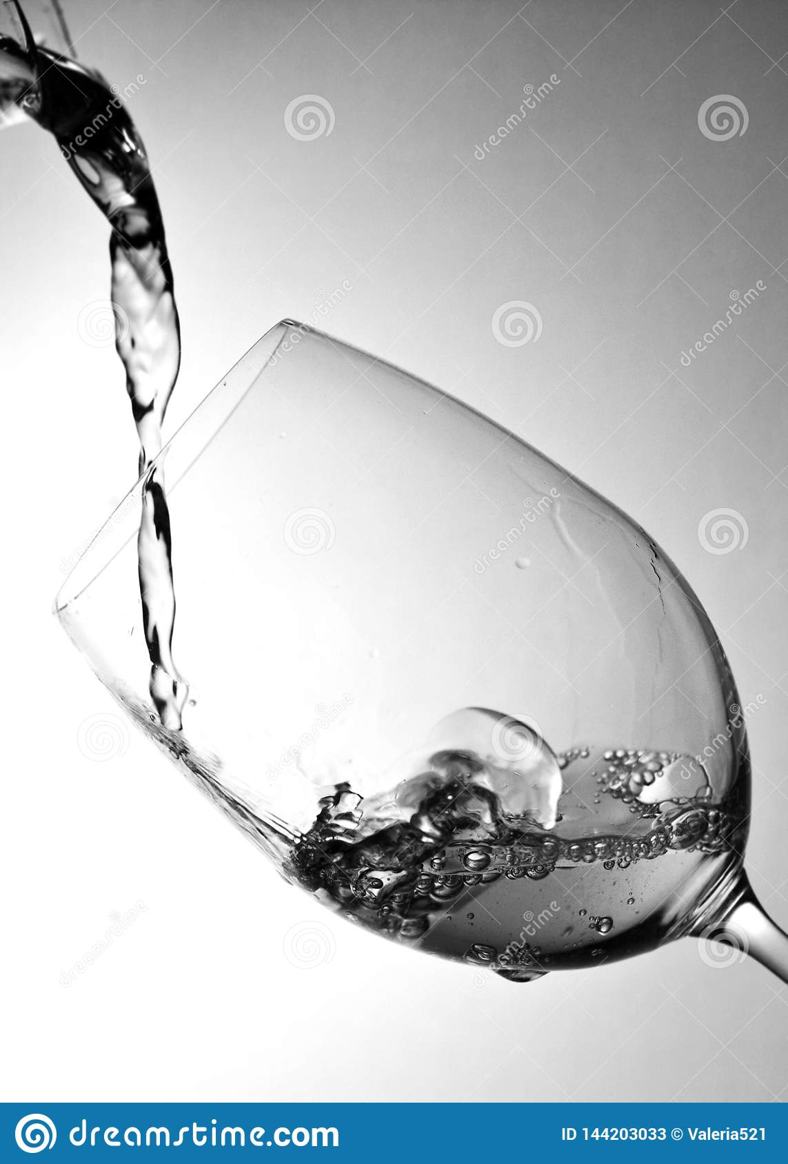 Water splashing into the glass on a gray background