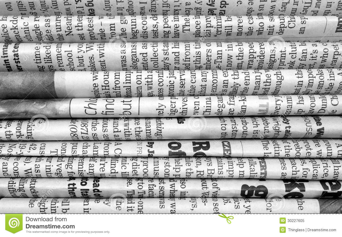A black and white photograph of english language newspapers folded and stacked to provide a background