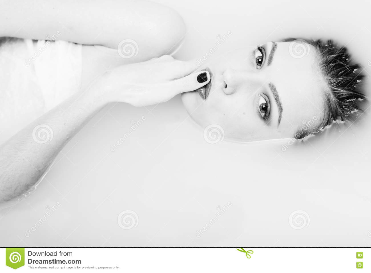 Black and white photography of beautiful tender young woman touching her lips with finger lying in the water on light background closeup portrait