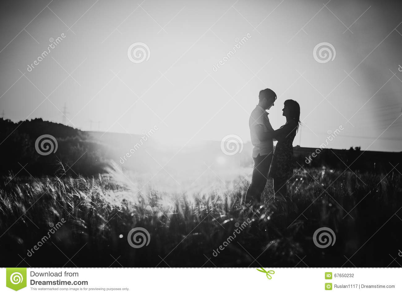 Black white photography romantic couple standing and kissing on background summer meadow