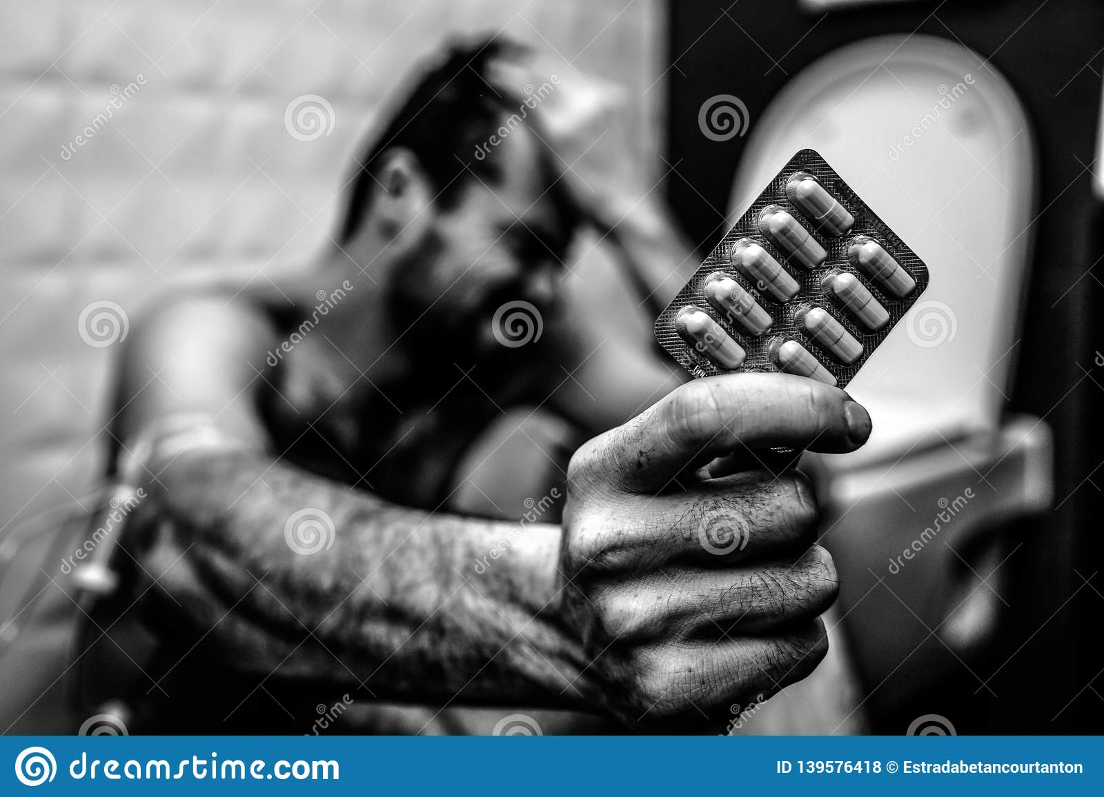 Black and white picture of young man sit on floor in rest room and hold plate of pills. Hand is wrapped with plait for