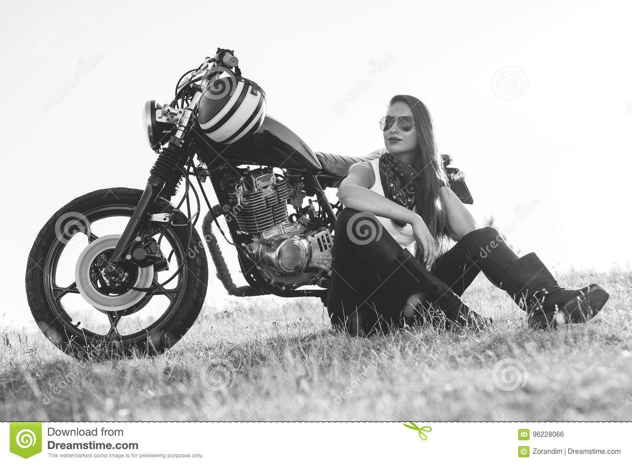 Black and white portrait of a beautiful biker woman sitting by her motorcycle