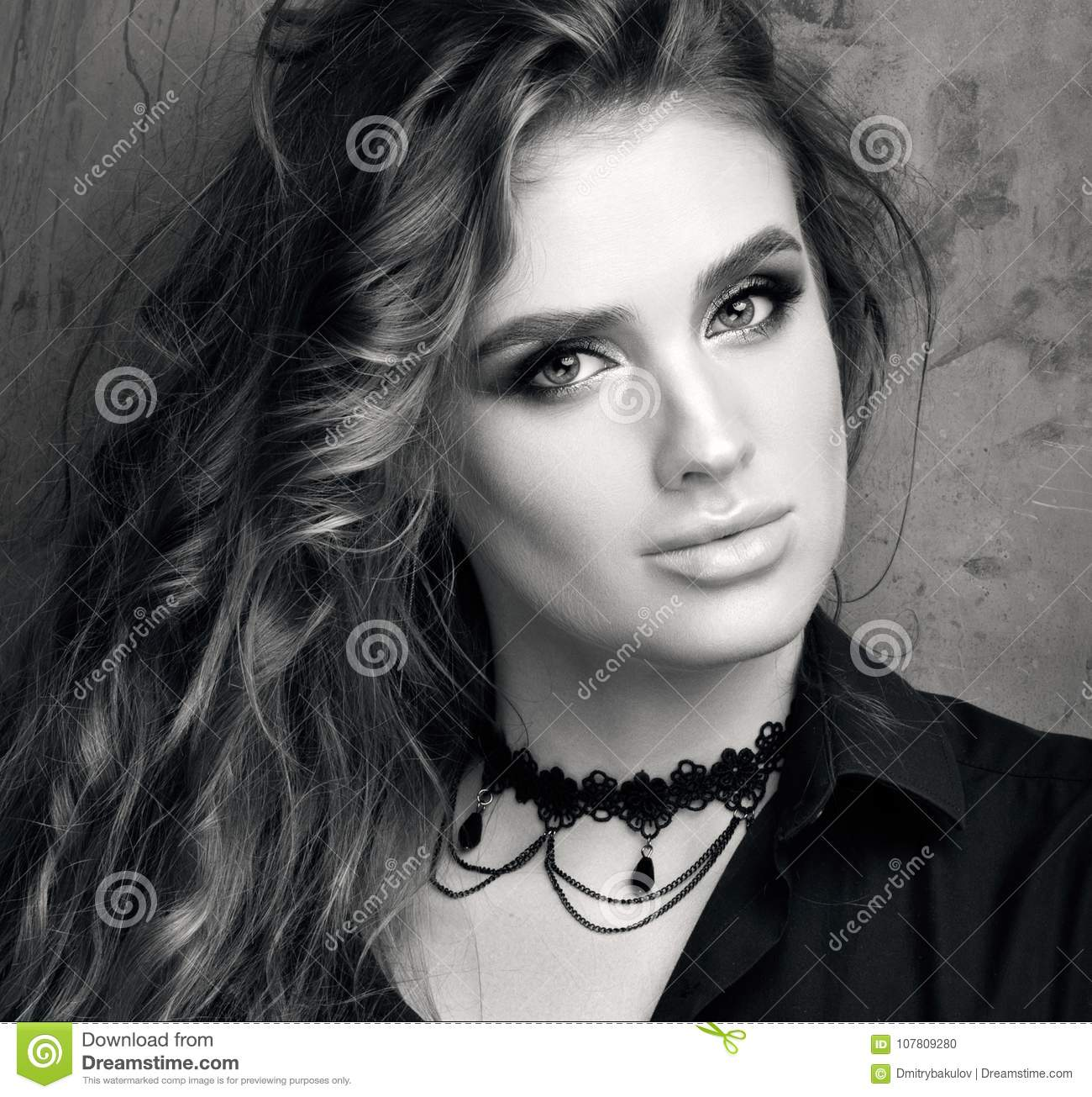 Black and white portrait of closeup up of a young woman in black shirt posing in front of a metal wall luxurious healthy hair and professional makeup
