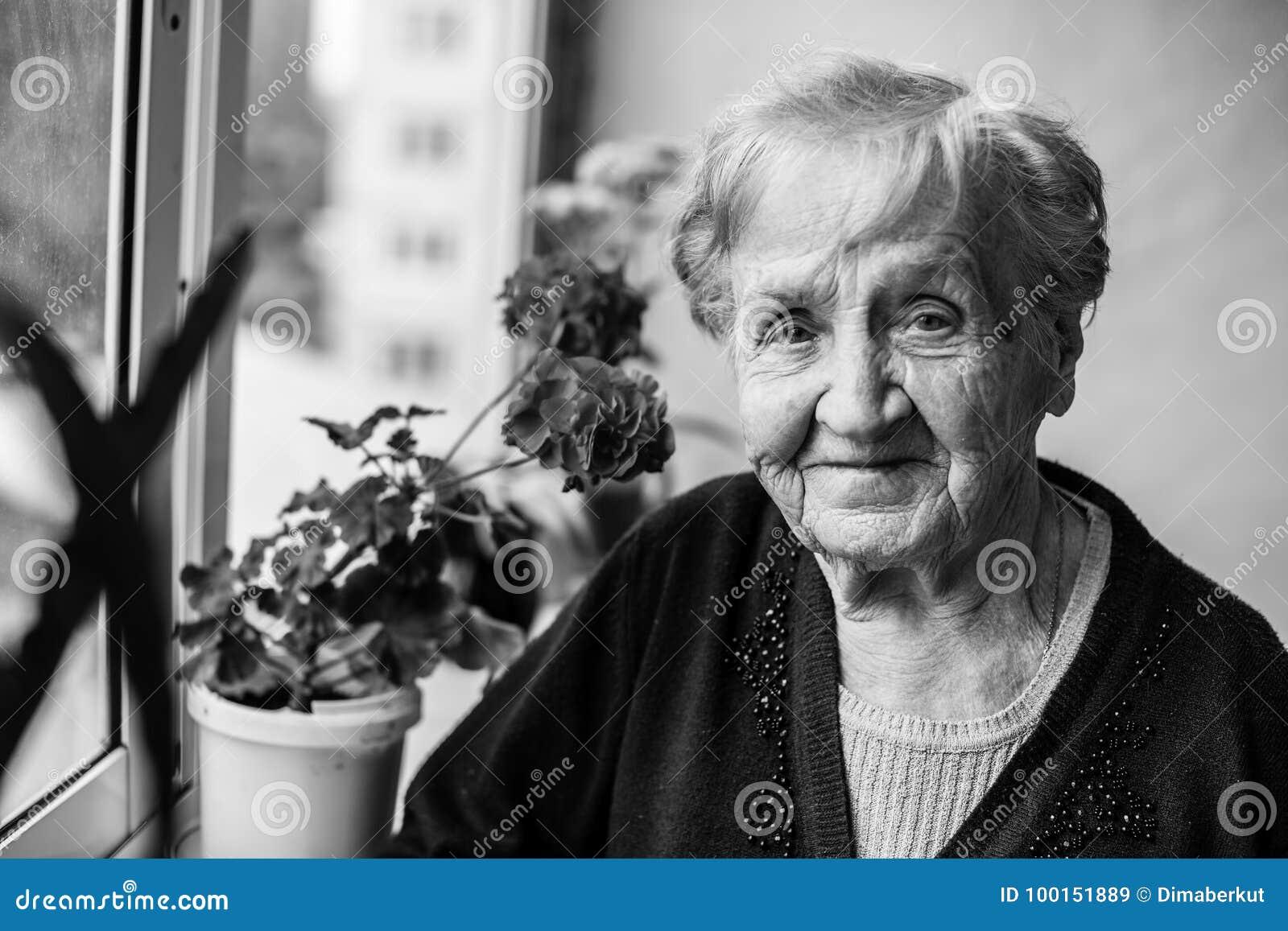 Portrait of an elderly woman on the balcony.