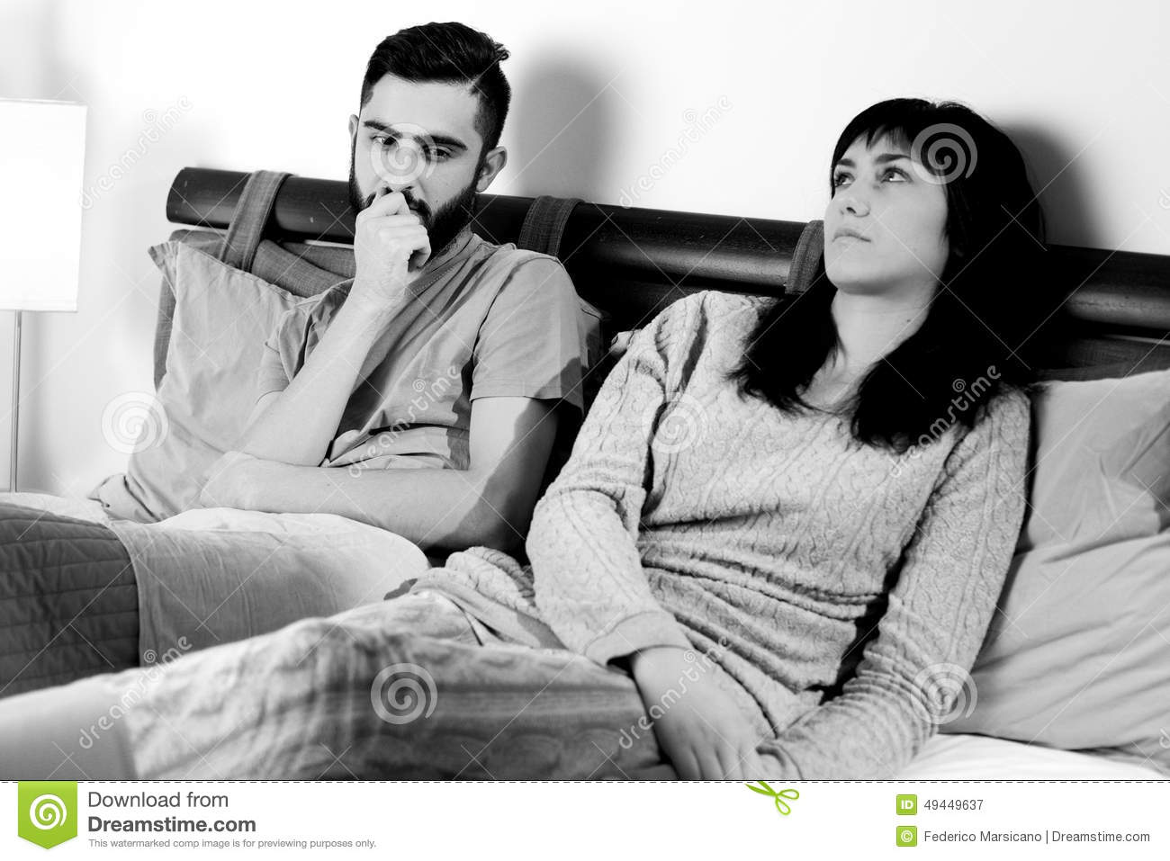 Black and white portrait of sad couple in bed after fight not talking