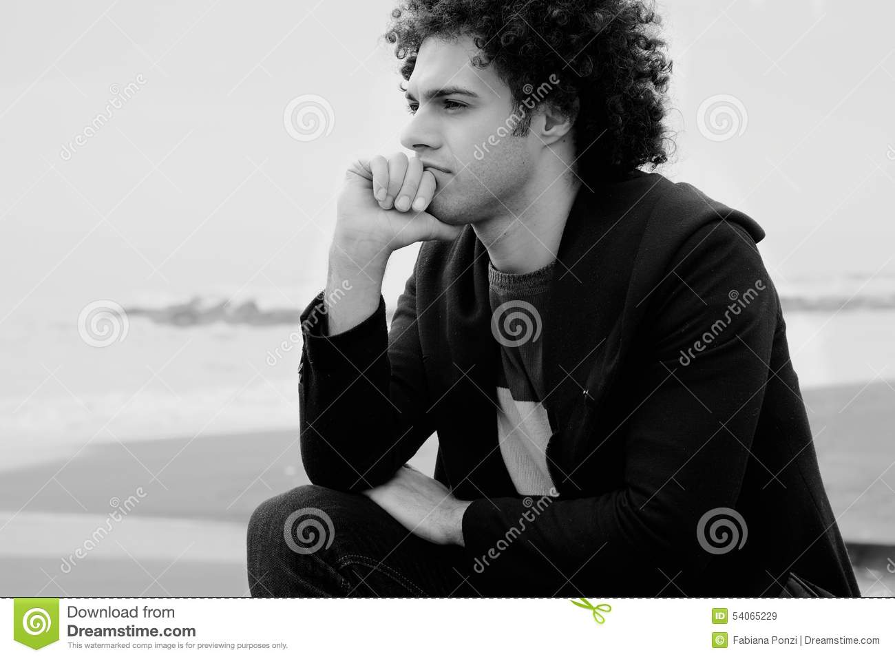 Black and white portrait of sad man in front of the ocean