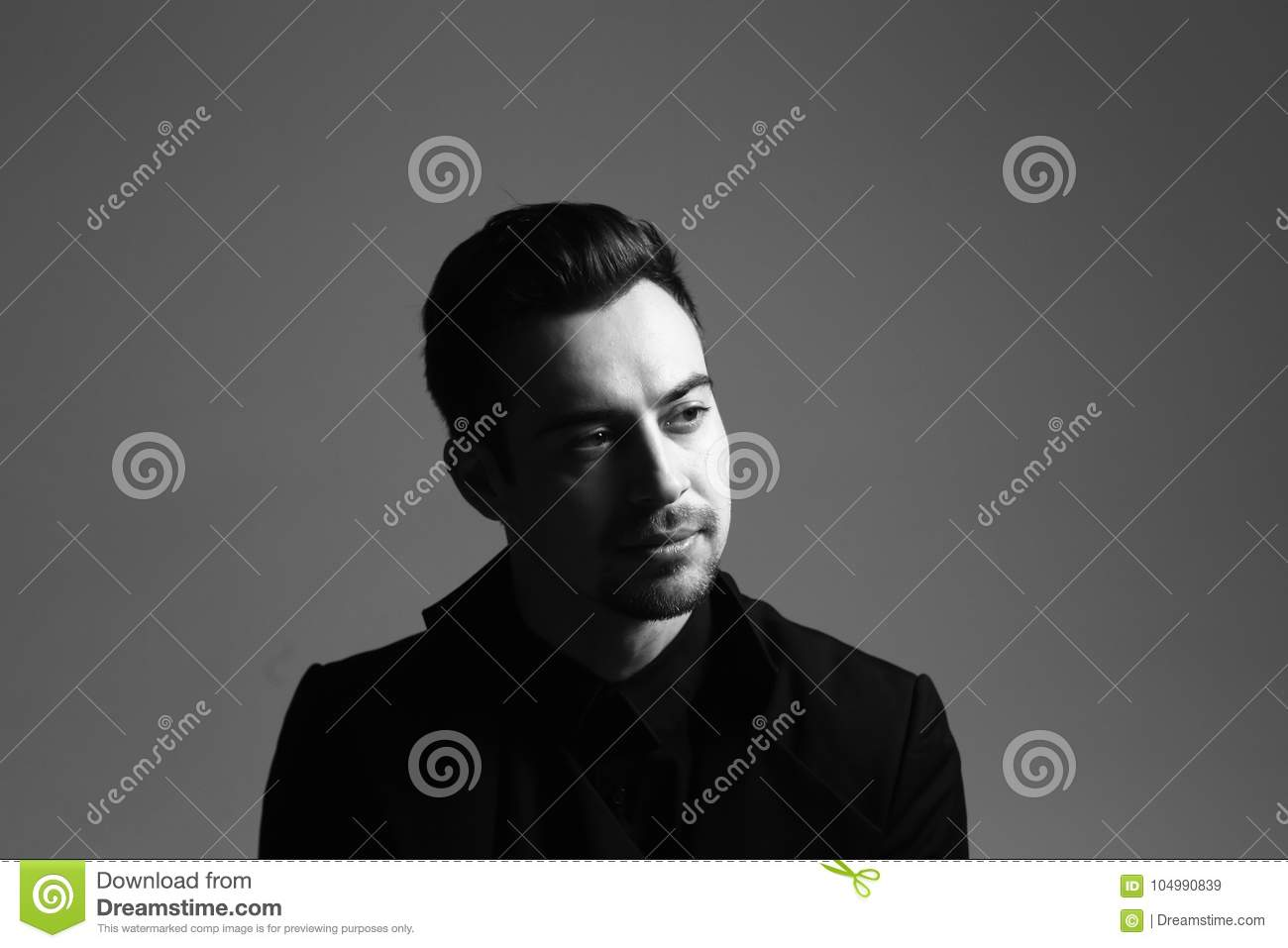 Black and white portrait of a serious young handsome man in a suit dramatic lighting