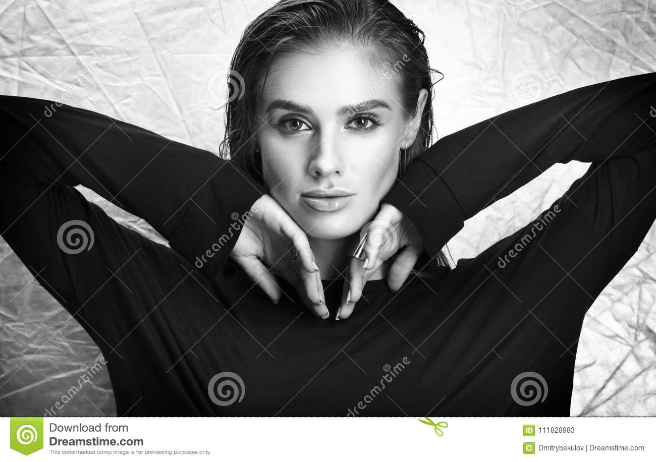 Black and white portrait of young woman in black wet hair and professional makeup