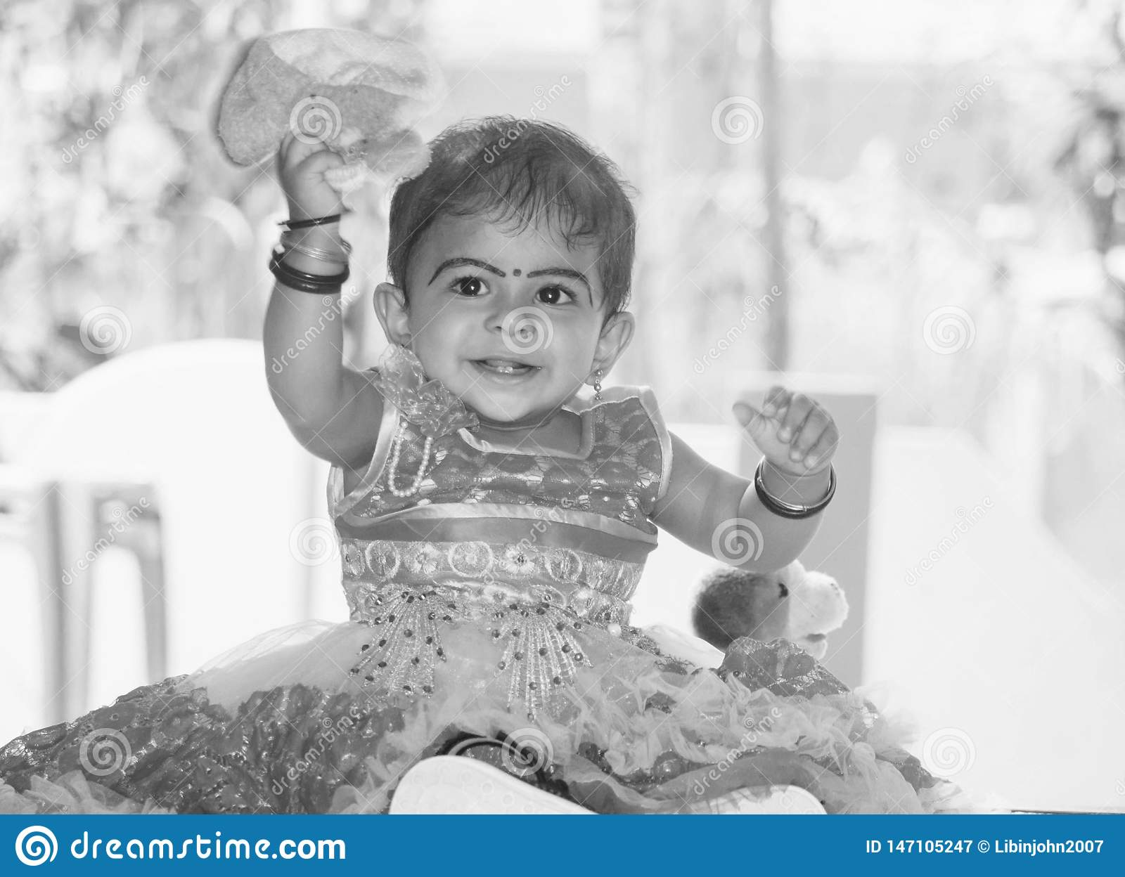 A black and white portrait of a smiling cute Indian child girl