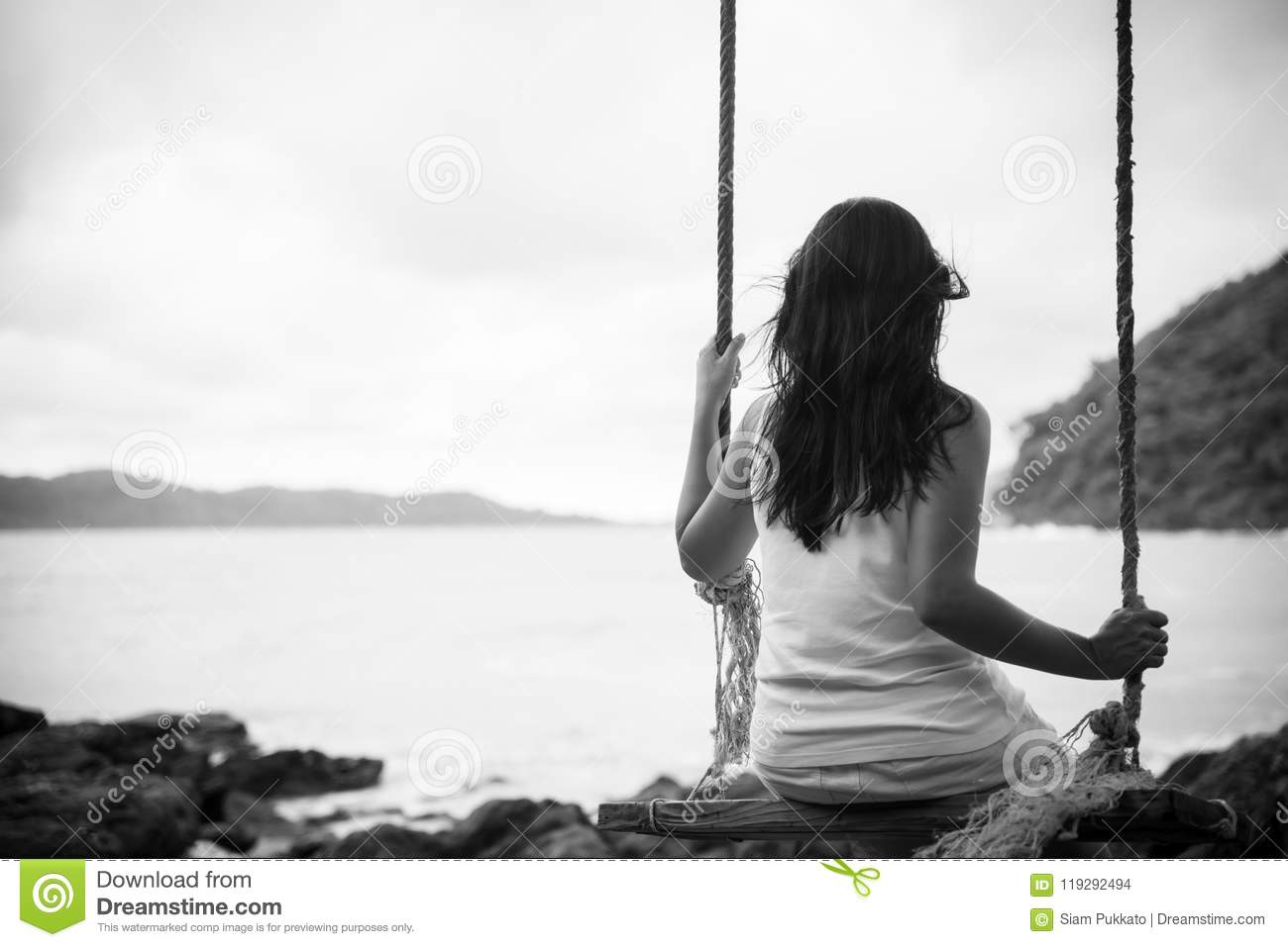 Black and white of sad and lonely woman sitting alone