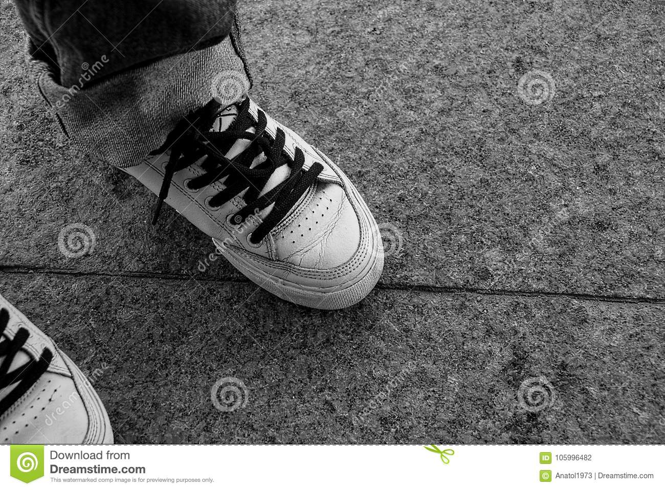 757a1fc171a45c White Sneakers With Black Laces On Their Feet On The Stone Floor ...