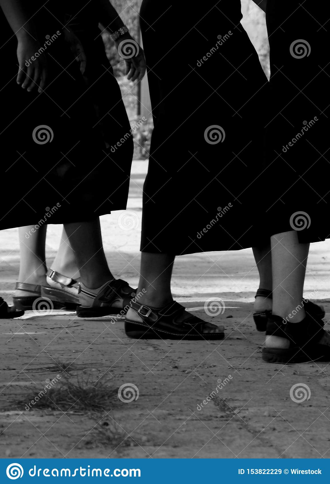 Black and white shot of female legs wearing sandals and skirts