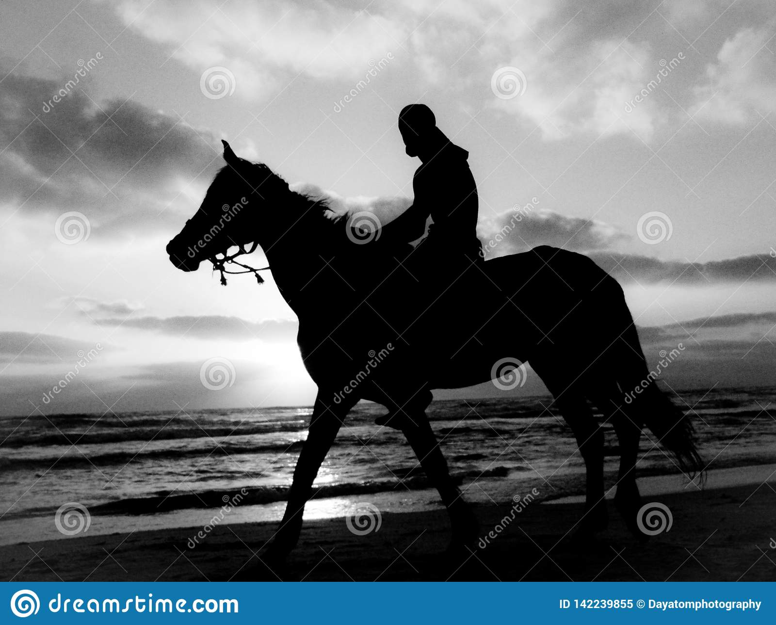 Black and white silhouette of a man riding a horse on a sandy beach under a cloudy sky during sunset
