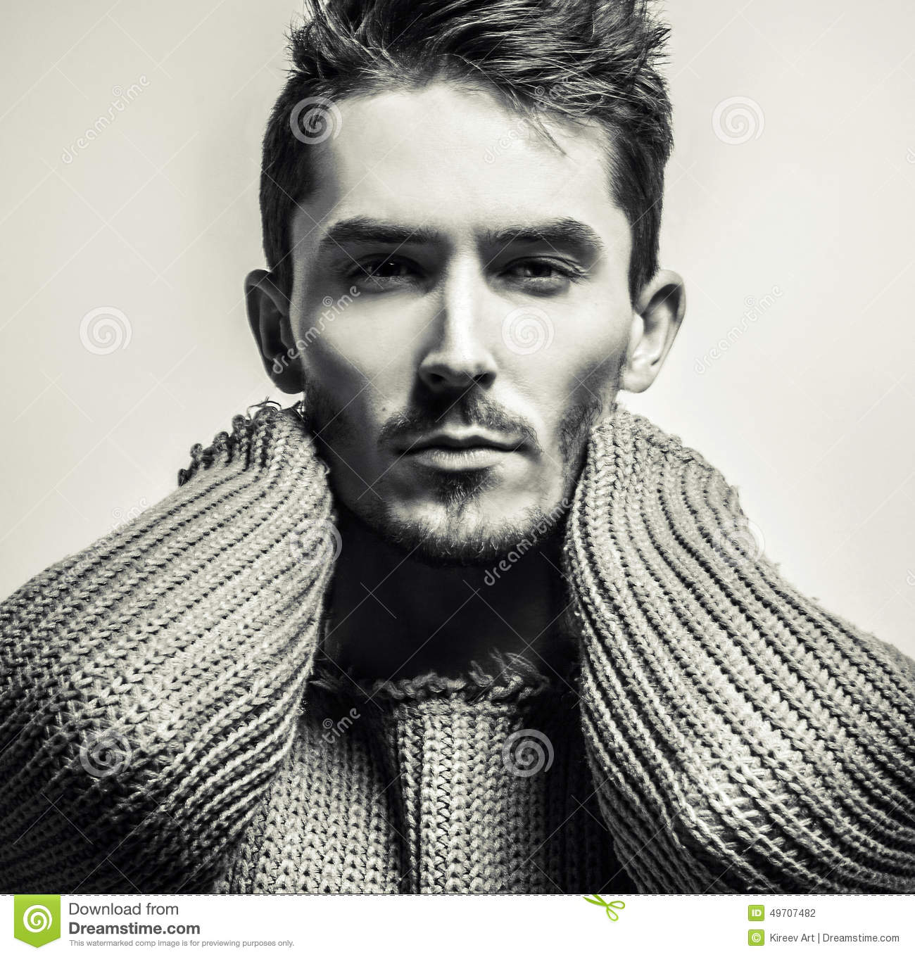 Black white studio portrait of young handsome man in knitted sweater