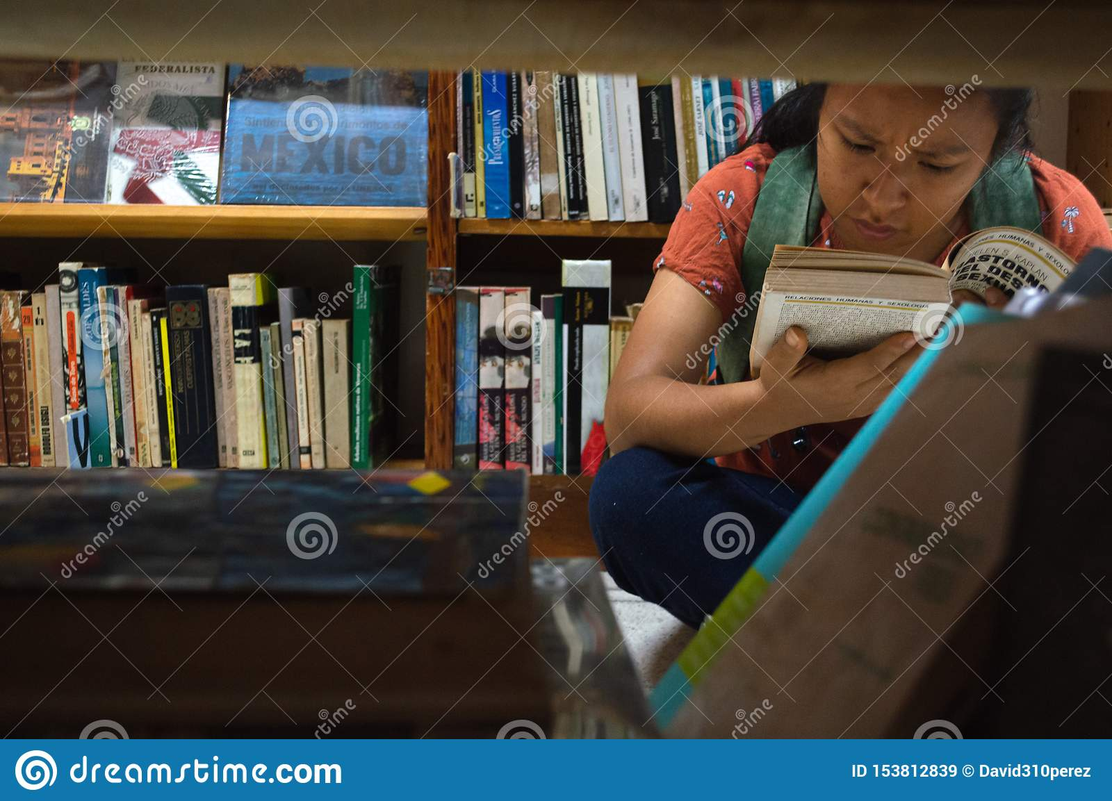 Black woman with book in her hands in a library