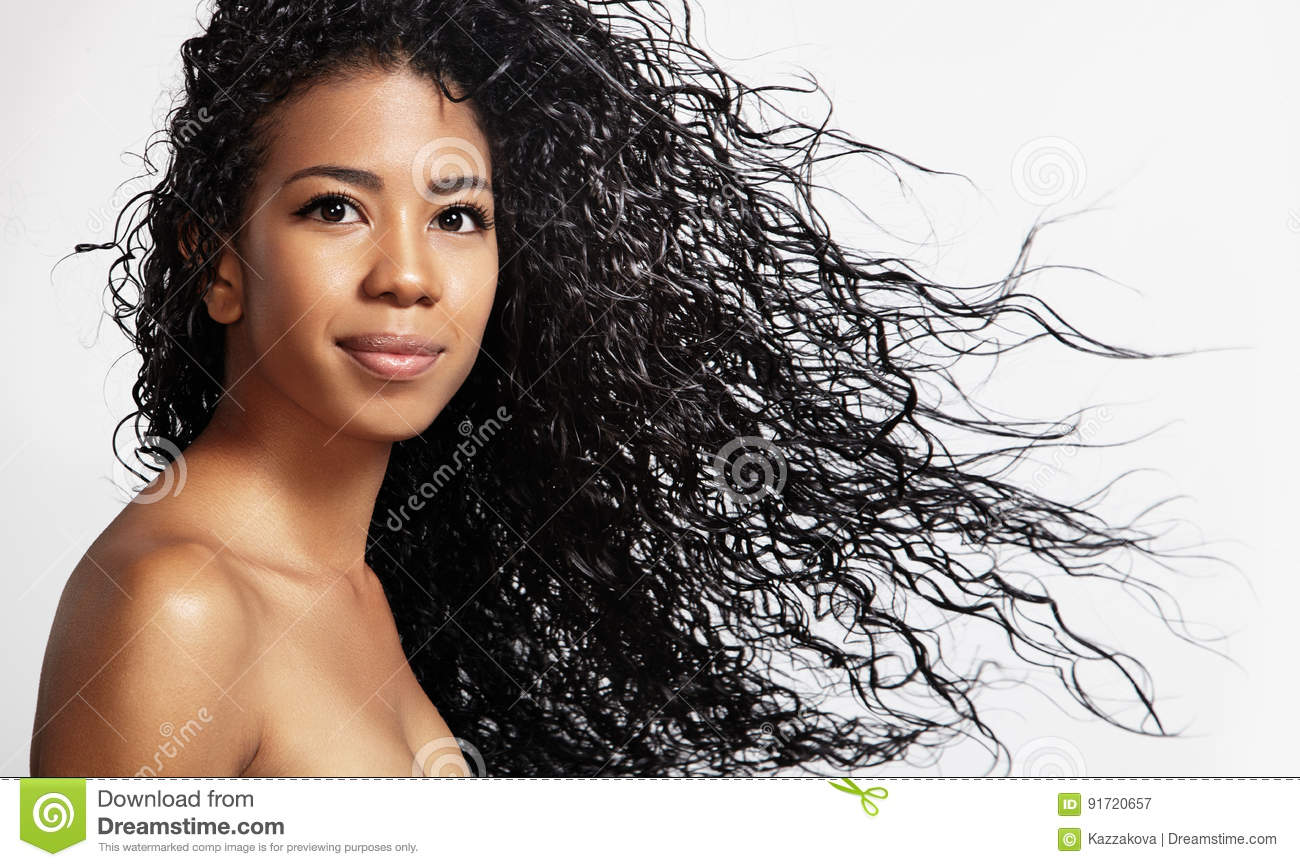 Black woman with a curly hair in air