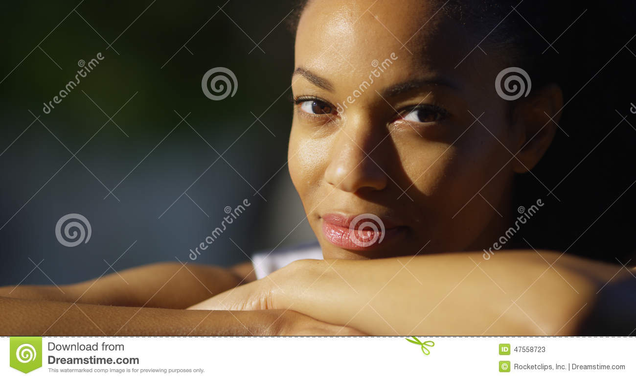 Black woman resting on arms looking at camera
