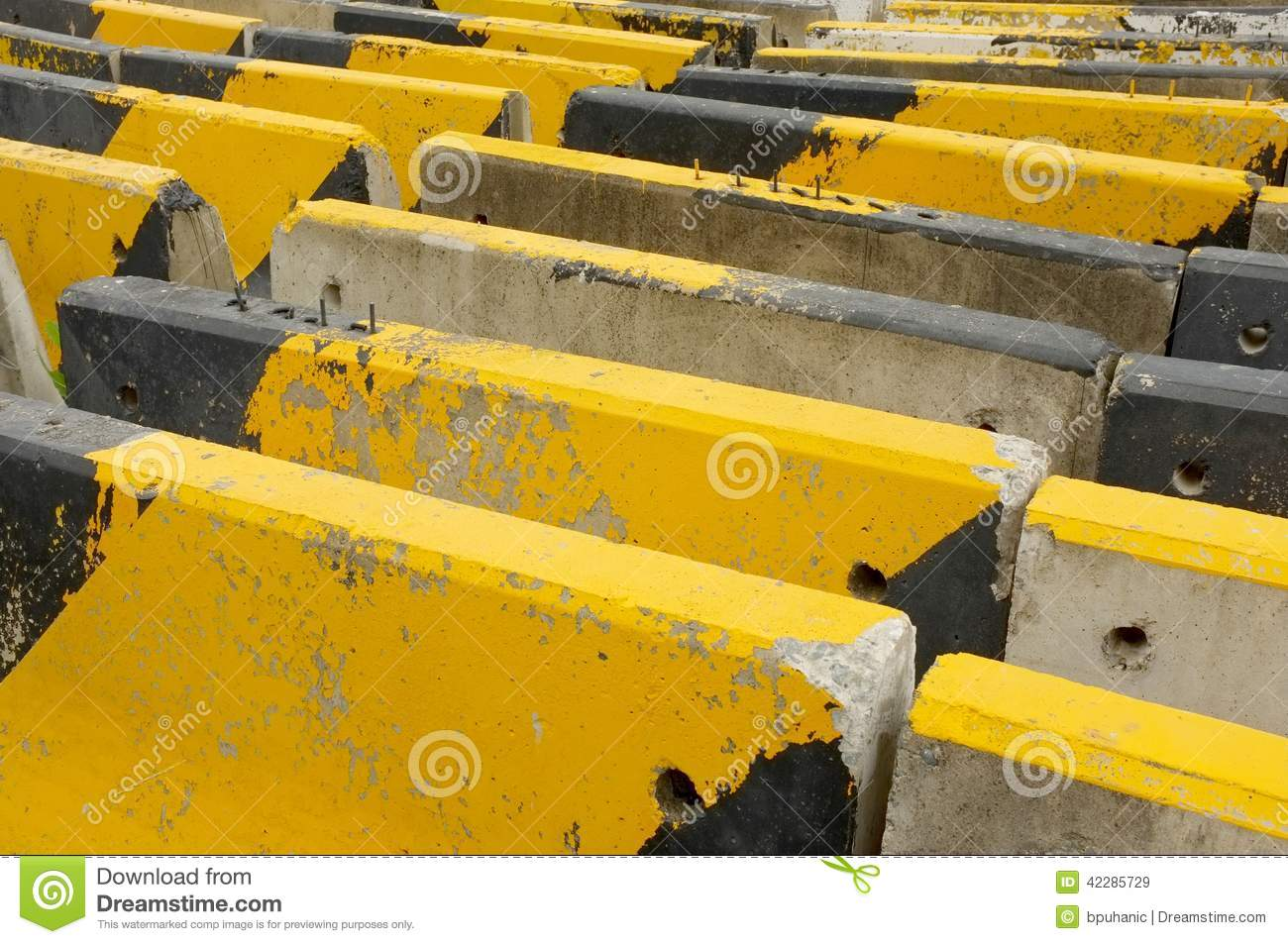 Black and yellow concrete road barriers or blocks