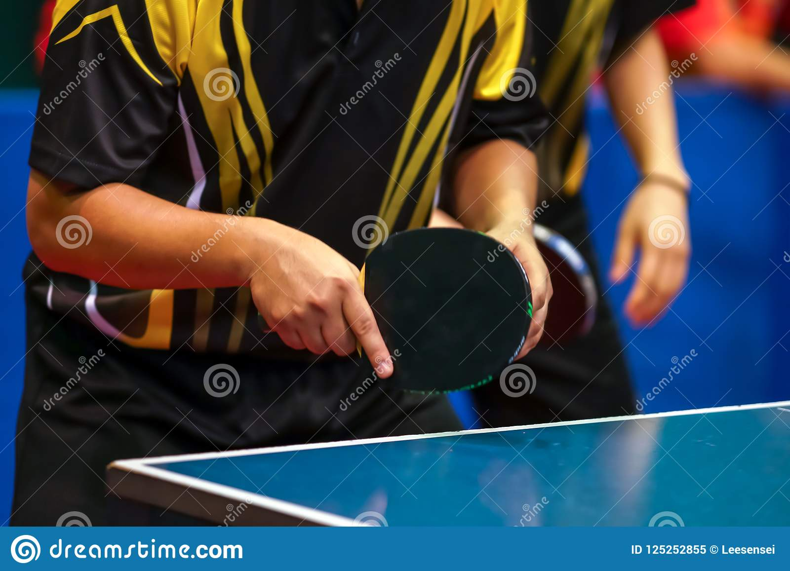 Black yellow shirt men playing double table tennis