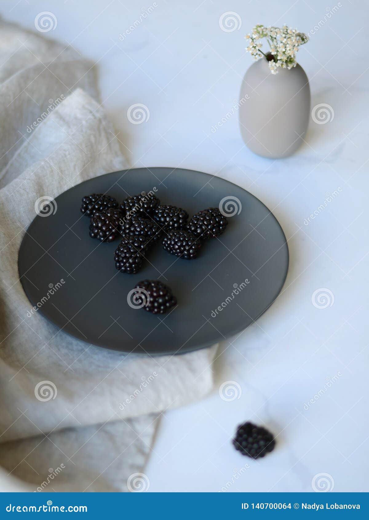 Blackberry auf einer grauen Platte und einem Vase