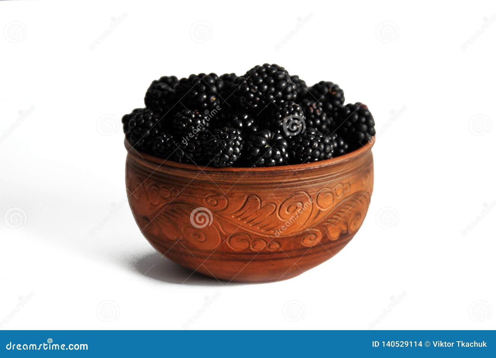 Blackberry-bessen in aardewerk op wit wordt geïsoleerd dat