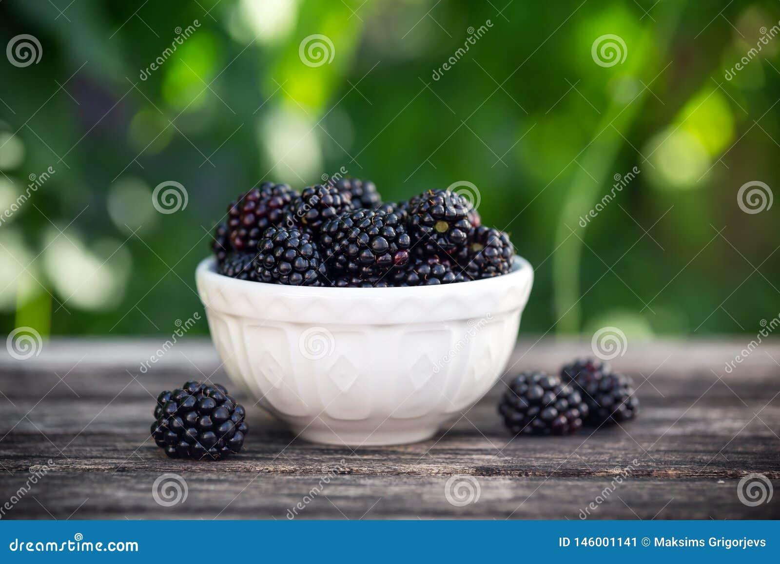 Blackberry i liten bunke på trätabellen i trädgård