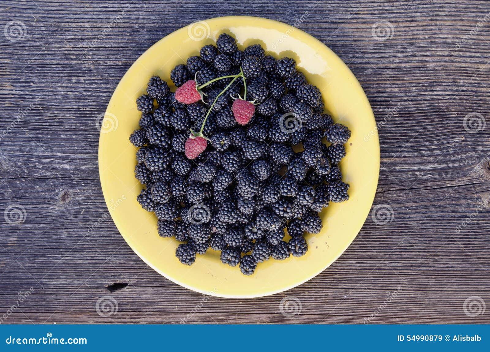Blackberry och hallon i gul keramisk platta