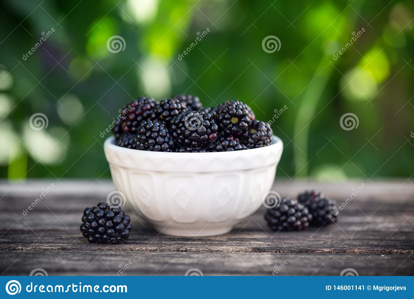 Blackberry in small bowl on wooden table in garden