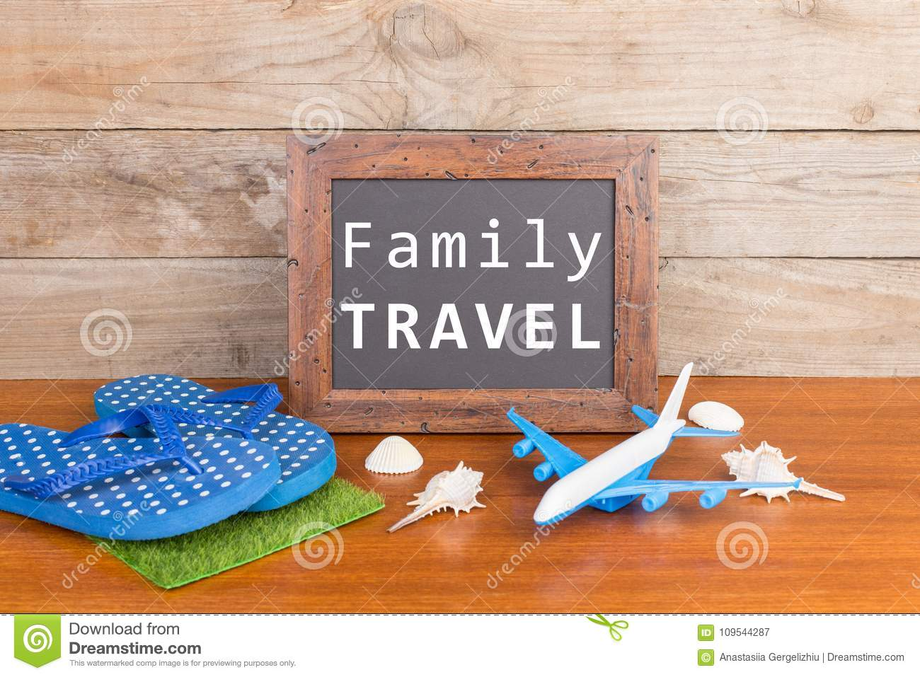 blackboard with text & x22;Family travel& x22;, plane, flip flops, seashells on brown wooden background