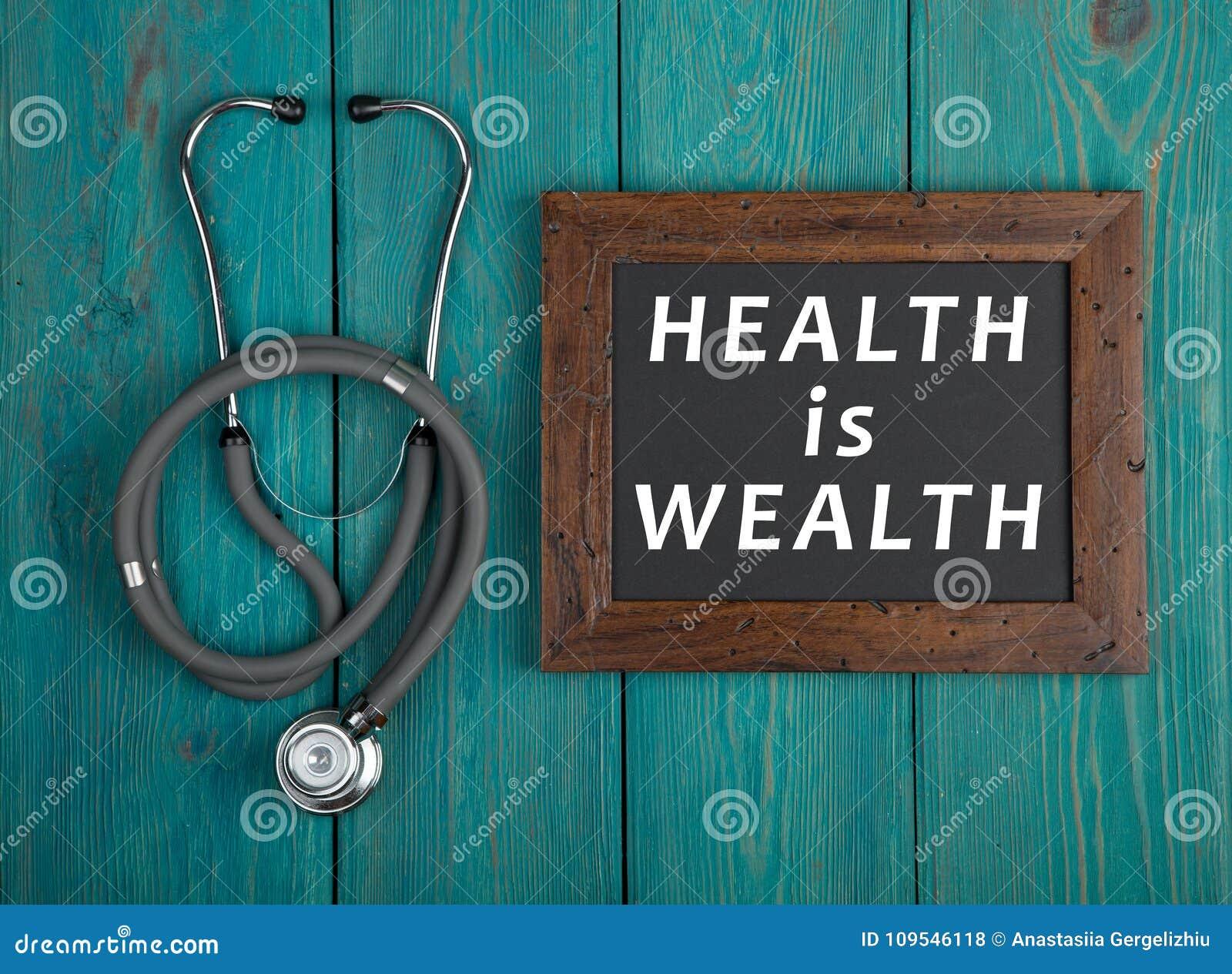 Blackboard z tekstem & x22; Zdrowie jest wealth& x22; i stetoskop na błękitnym drewnianym tle