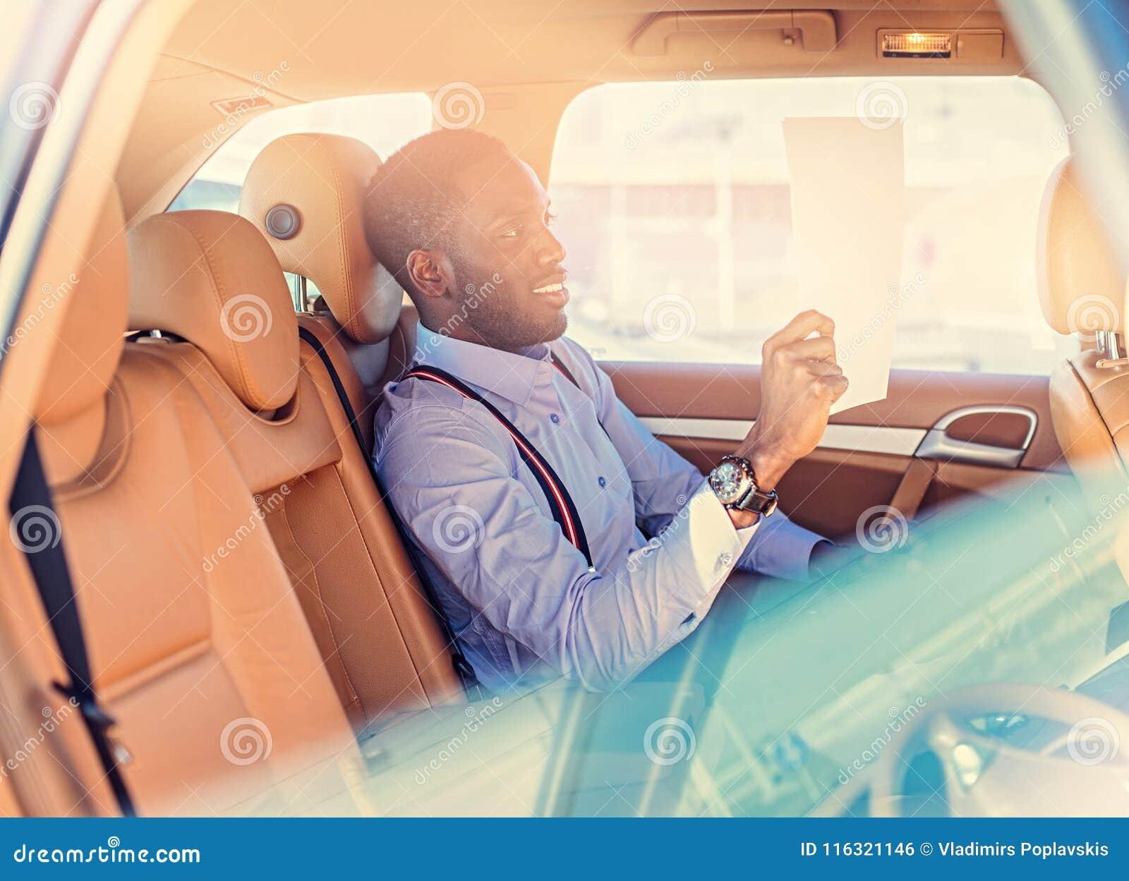 Blackman in einem blauen Hemd sitzt auf Auto ` s Rücksitz