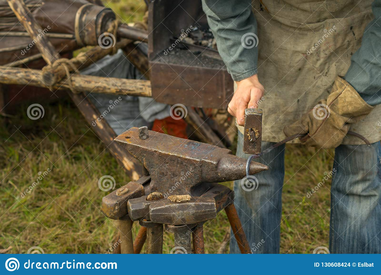 Blacksmith working at the anvil in the summer