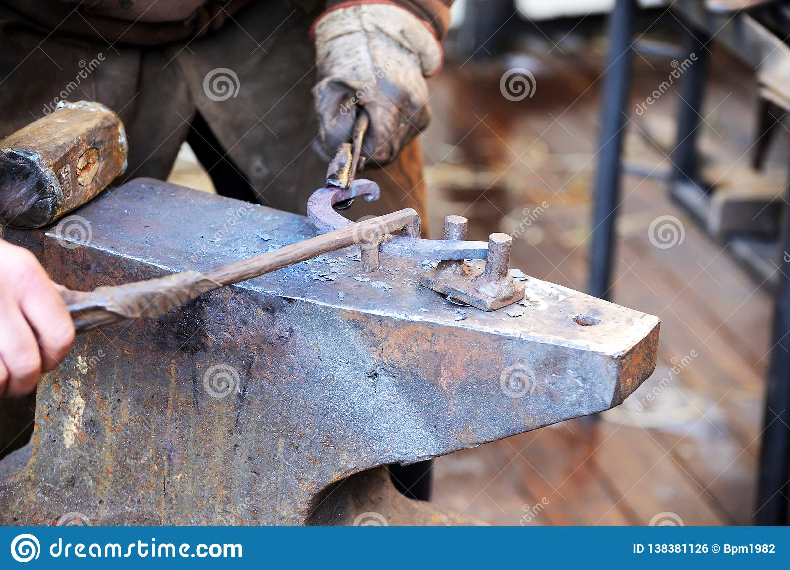Blacksmith Working Metal With Hammer On The Anvil Stock