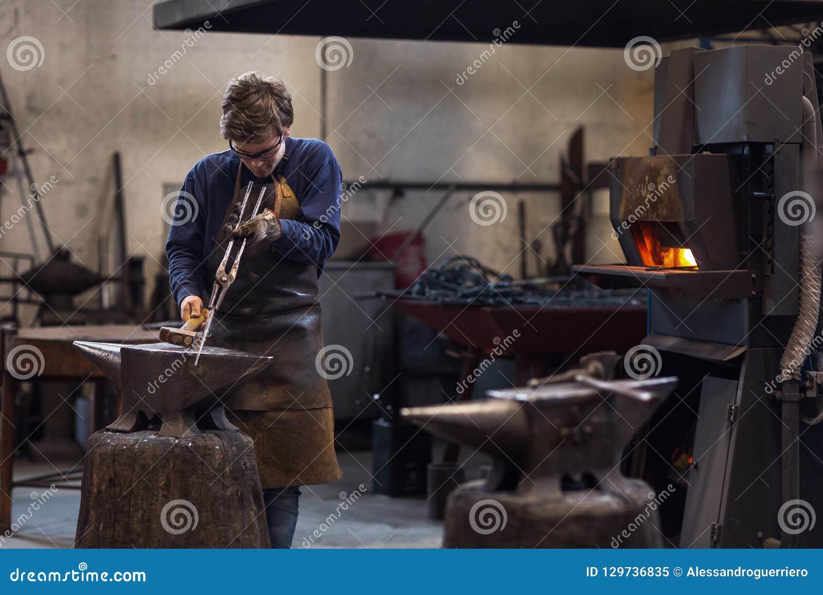 Blaksmith novo que trabalha com metal quente em uma oficina