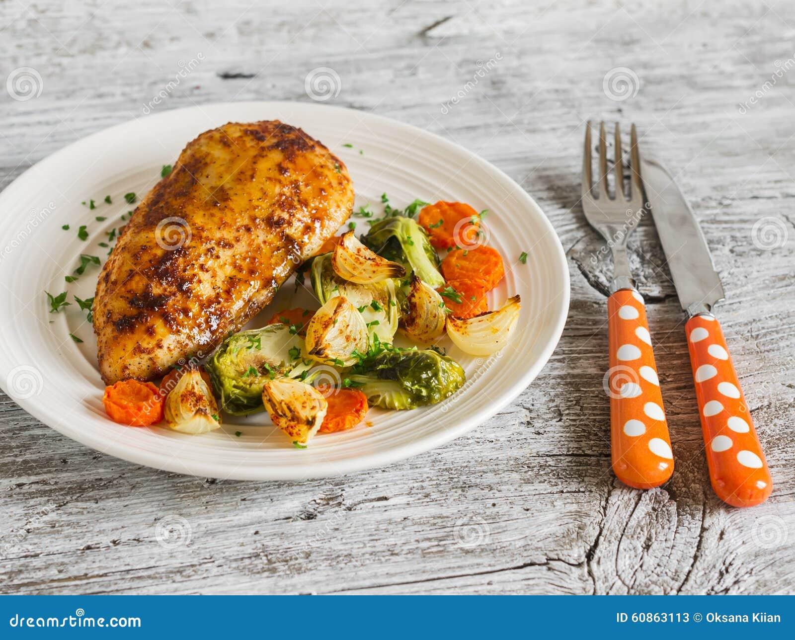 Blanc de poulet cuit au four avec des choux, des oignons et des carottes de bruxelles d un plat blanc sur la surface en bois