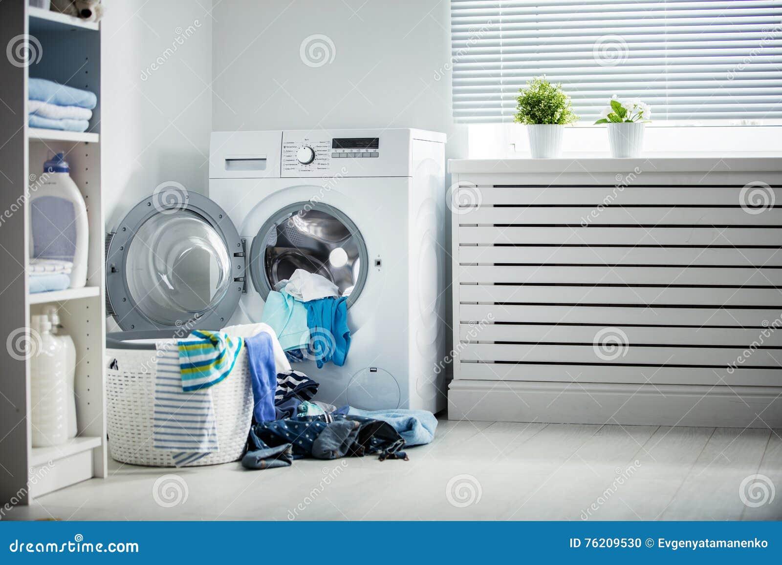 Blanchisserie Une machine à laver et une pile des vêtements sales