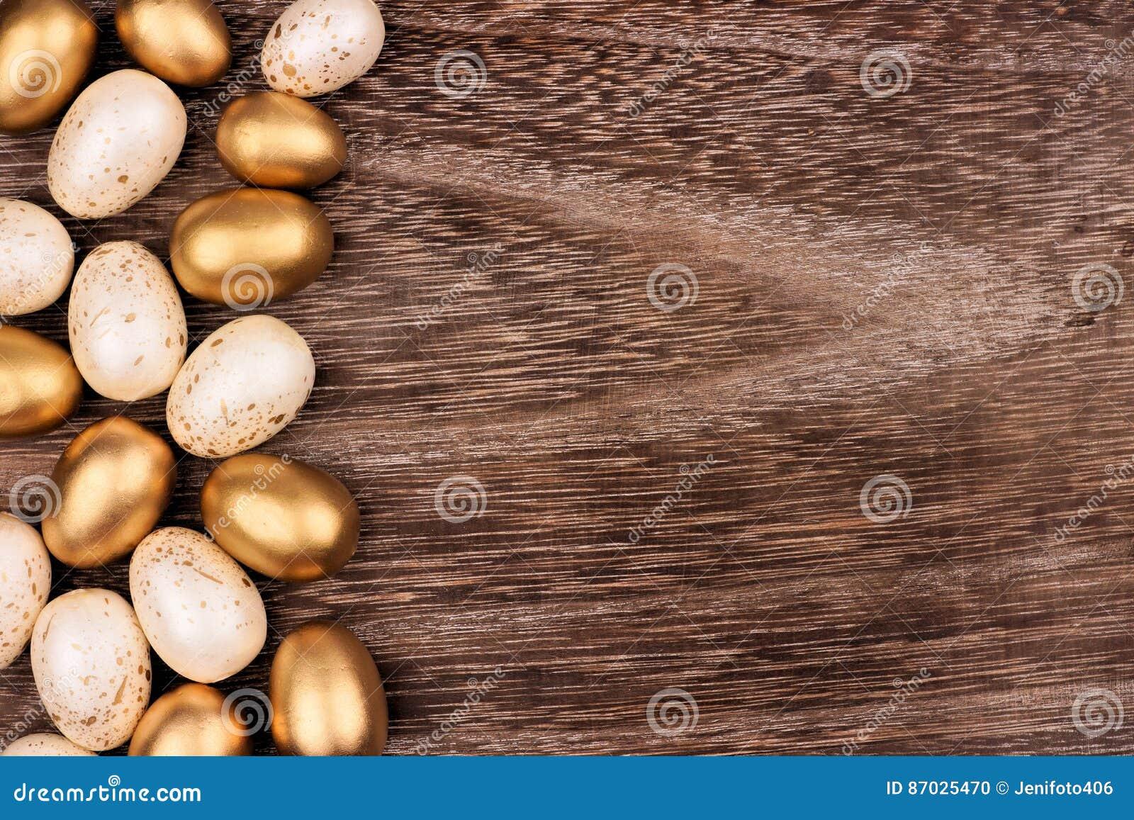 Blanco y frontera del lado del huevo de Pascua del oro sobre la madera rústica