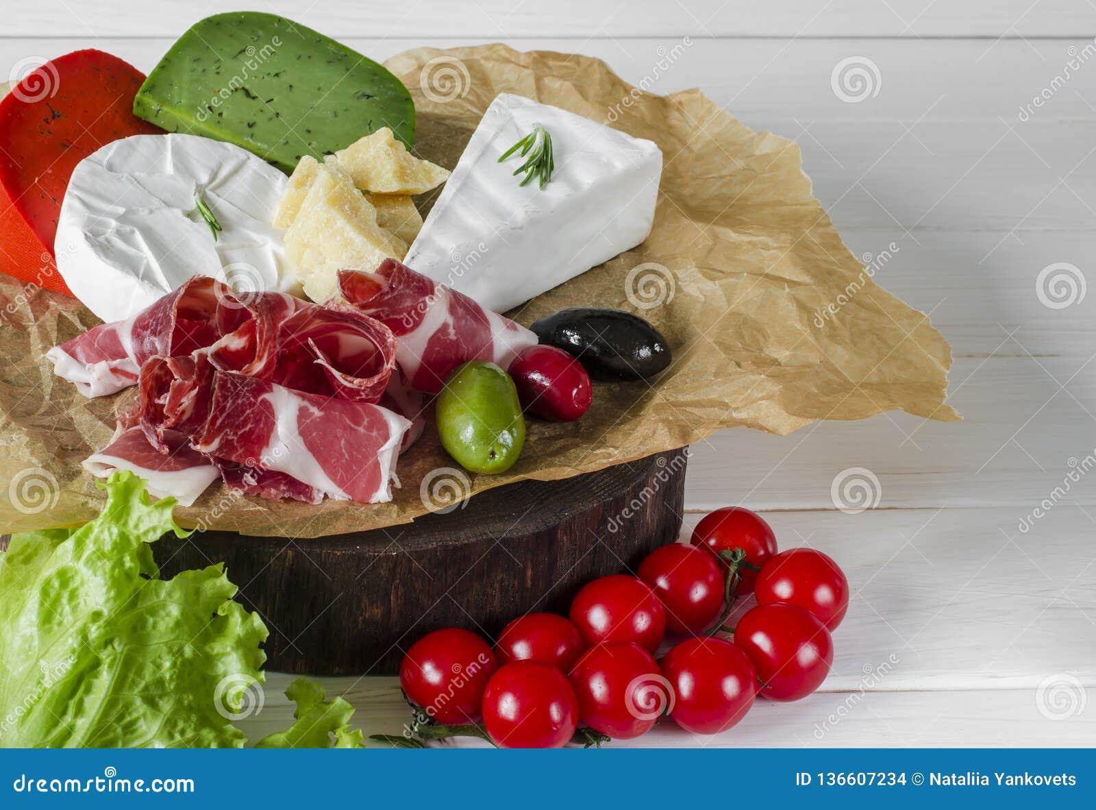 Blanda ost och kött på vit bakgrund på träbräde med druvor, honung, muttrar, tomater och basilika Top beskådar