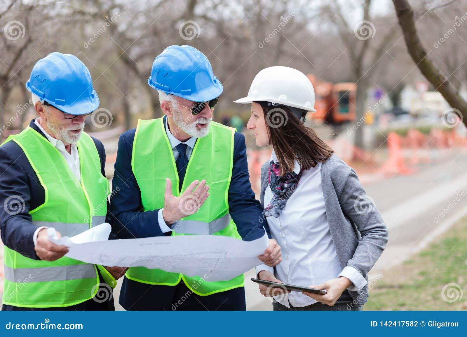 Blandad grupp av arkitekter och affärspartners som diskuterar projektdetaljer på en konstruktionsplats
