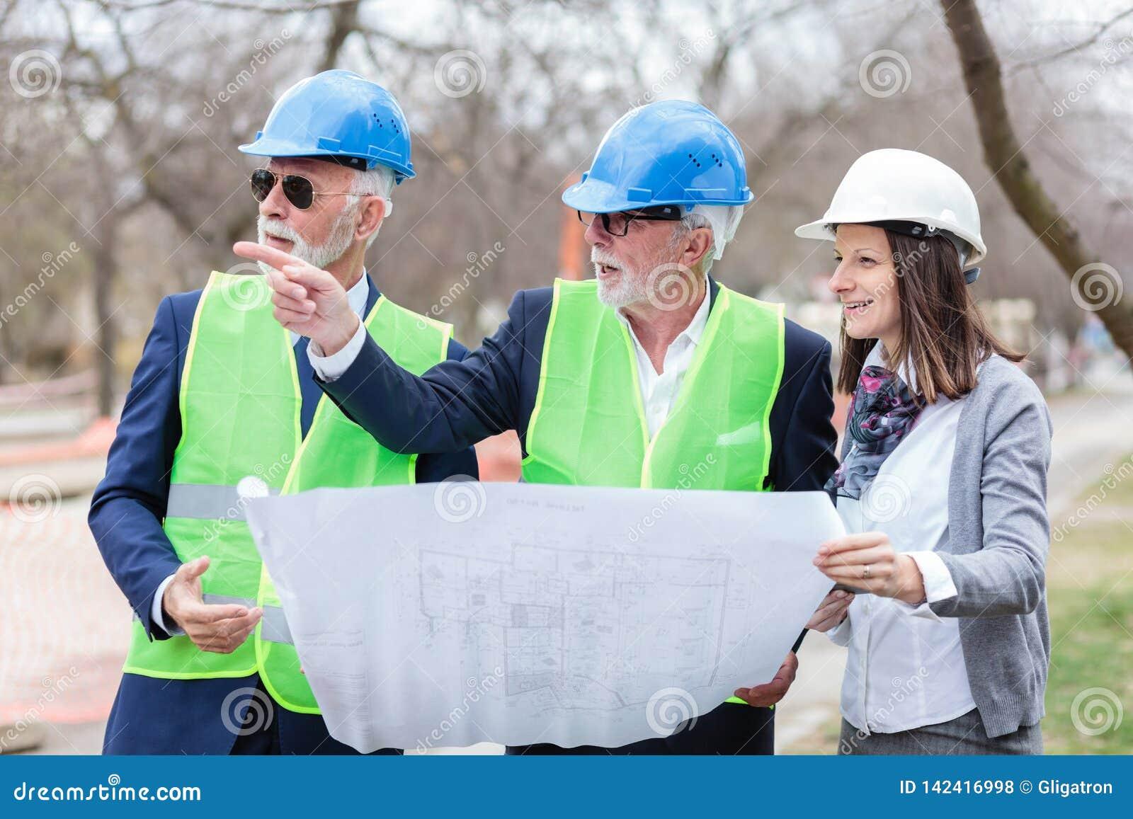 Blandad grupp av arkitekter och affärspartners som diskuterar projektdetaljer under kontroll av en konstruktionsplats
