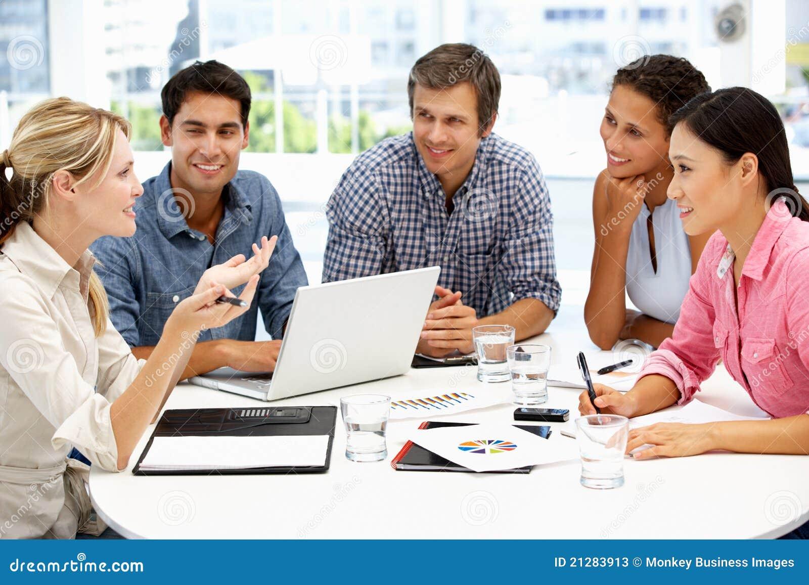 Blandad grupp runt om tabellen i affärsmöte