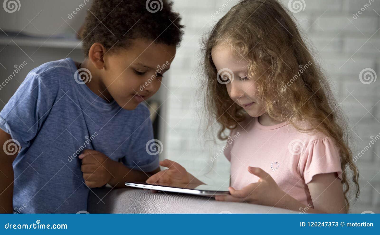 Blandad-lopp barn som håller ögonen på deras favorit- tecknade filmer på minnestavlan, applikation