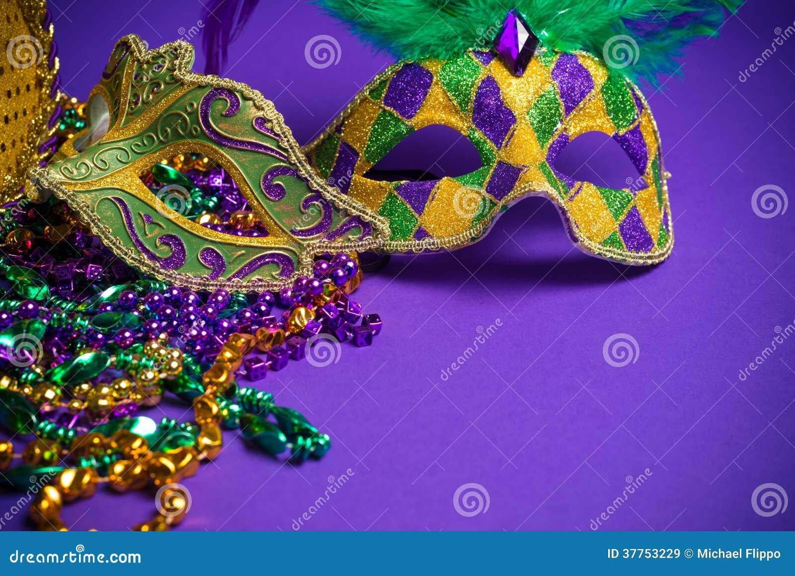 Blandad Mardi Gras eller Carnivale maskering på en purpurfärgad bakgrund