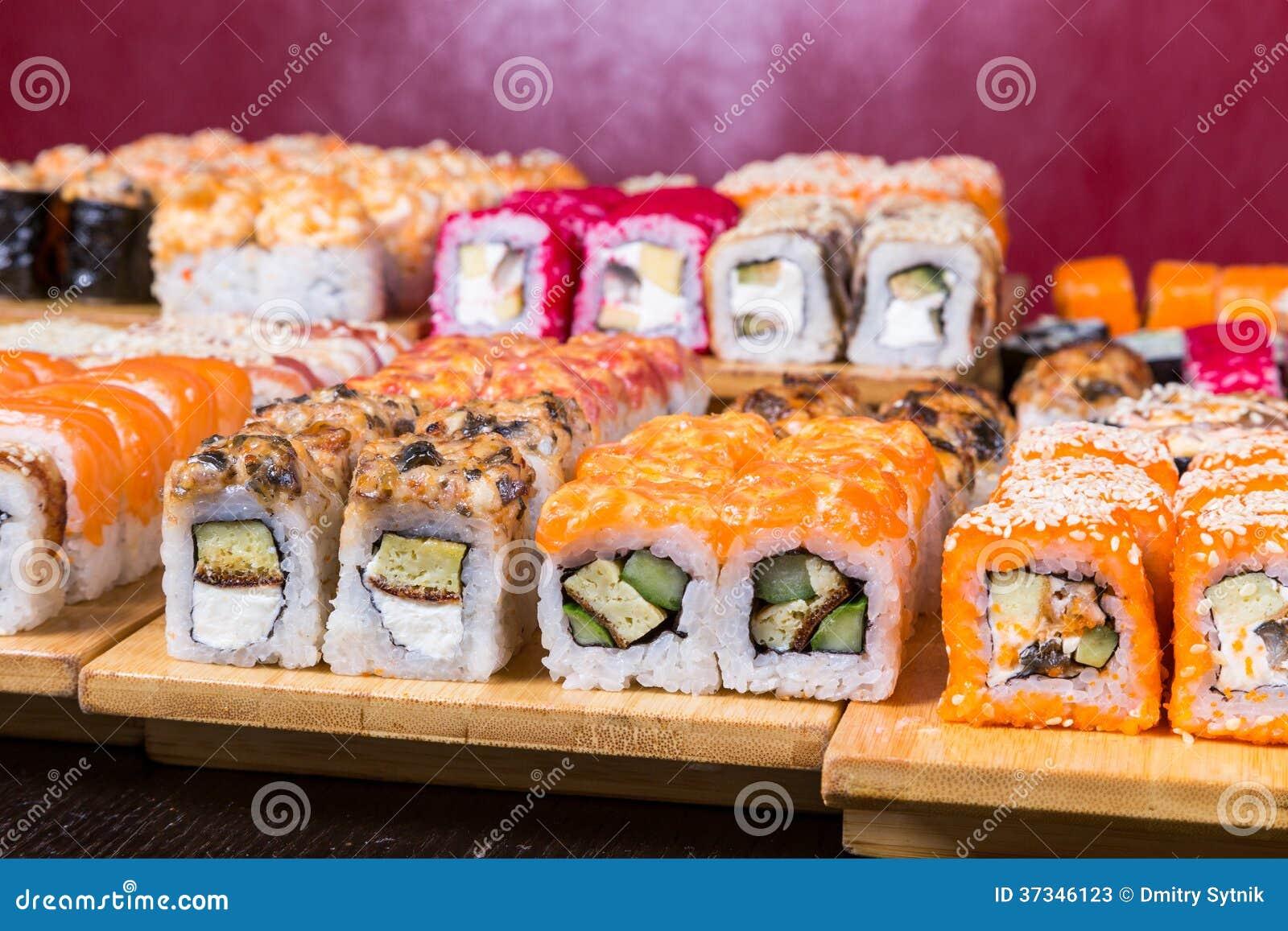 Blandad sushi och rullar på det wood brädet i mörkt ljus