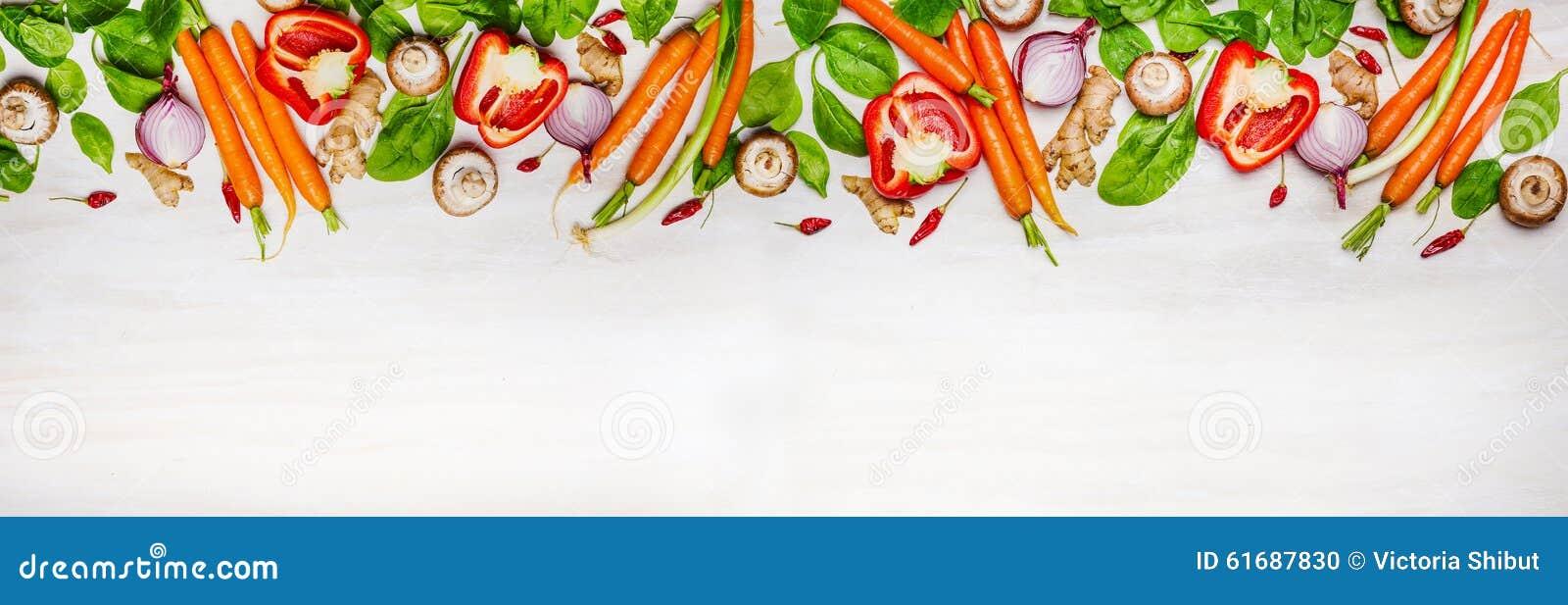 Blandade rå organiska grönsaker och ingredienser för sund matlagning på vit träbakgrund, bästa sikt, baner