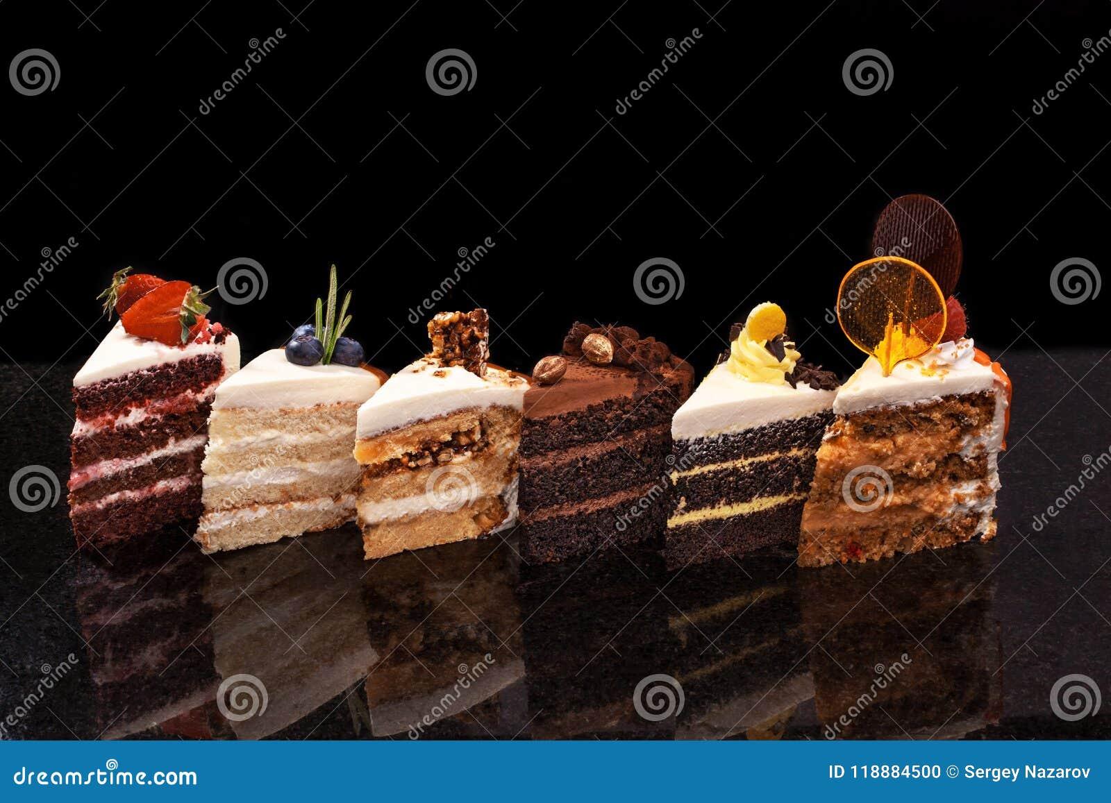 Blandade stora stycken av olika kakor: choklad hallon, jordgubbar, muttrar, blåbär Stycken av kakor på a