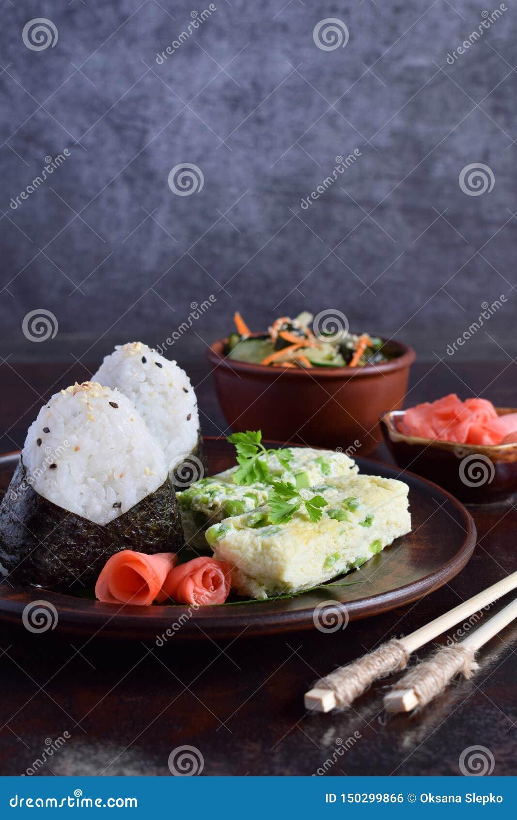 Blandning av japansk mat - ris klumpa ihop sig onigiri, omelett, den inlagda ingef?ran, sallad f?r sunomonowakamegurka och pinnar