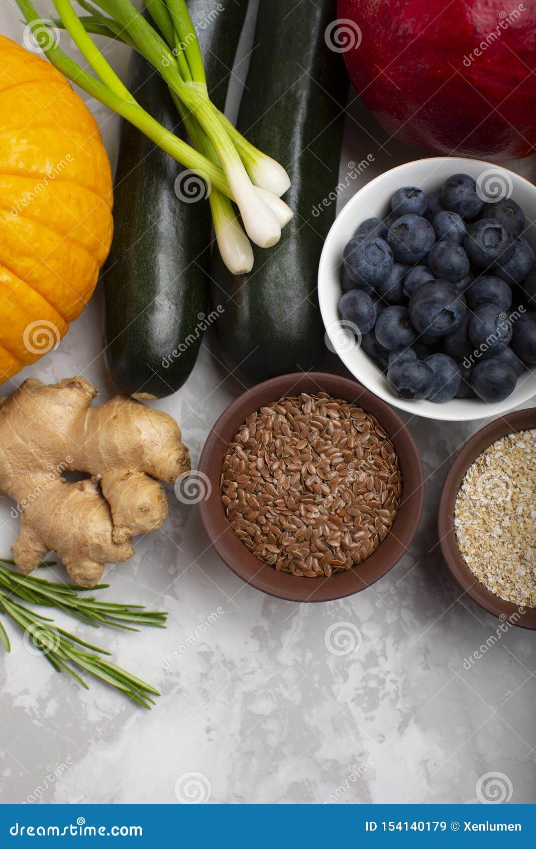 Blandning av nya sunda vegetariska ingredienser av grönsaker, frö, kli, frukt och bär på en grå cementbakgrund