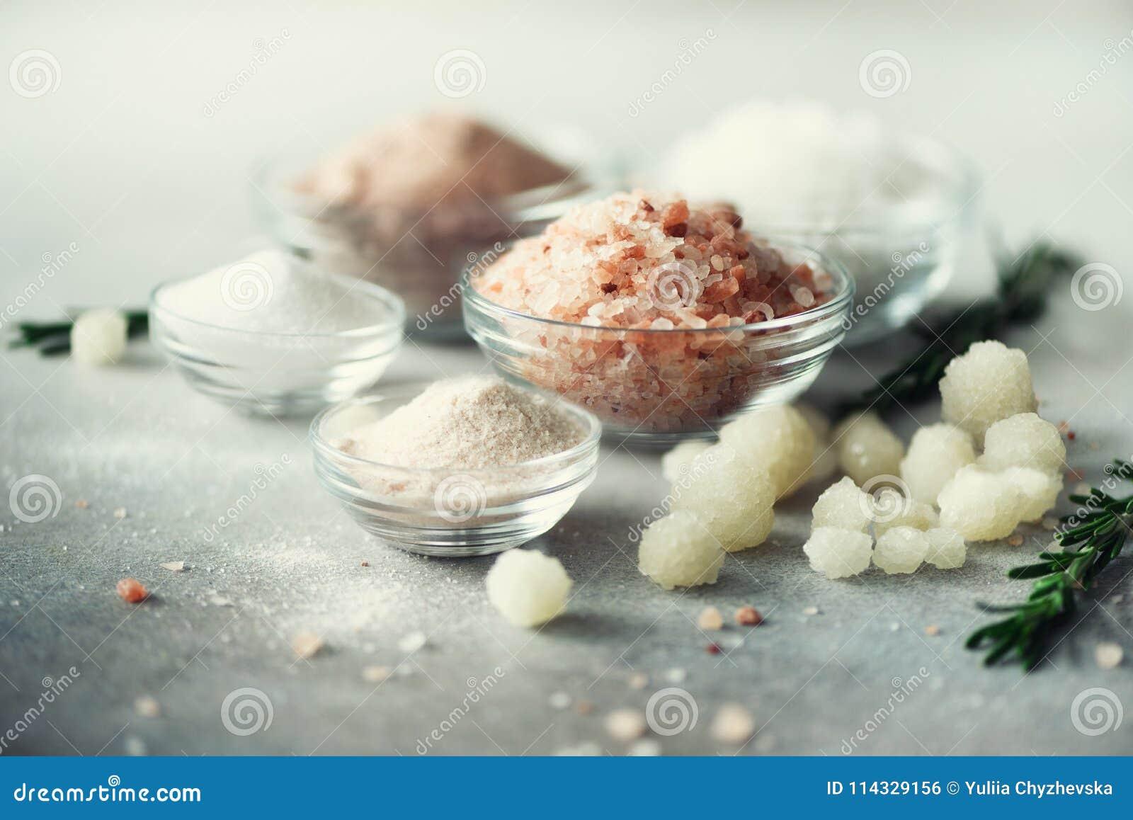Blandningen av olika salta typer på grå färger hårdnar bakgrund Havet saltar, svart och rosa Himalayan salta kristaller, pulver