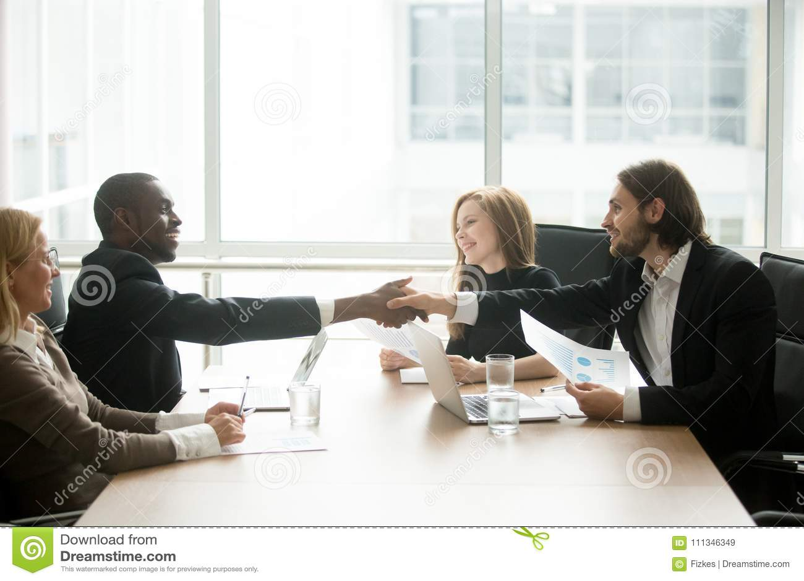 Blandras- affärsmän i dräkthandshaking på den utövande lagnollan